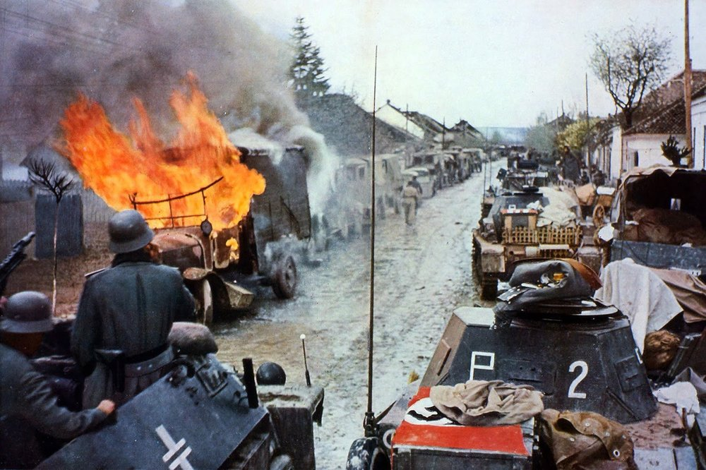 German armoured car Sd Kfz. 251 of the 14-20th motorised Corps are passing convoys of tanks Pz. Kpfw II and burning a truck.jpg
