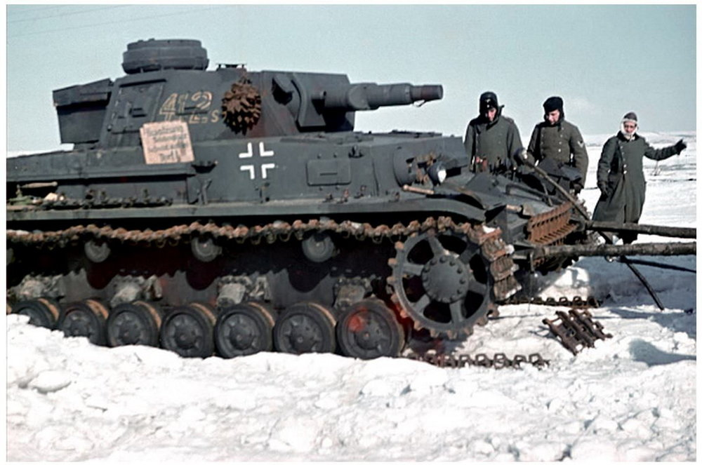 A Panzer 4 Ausf E, wearing it's standard grey paint scheme, is getting help with a broken track on the right side.jpg