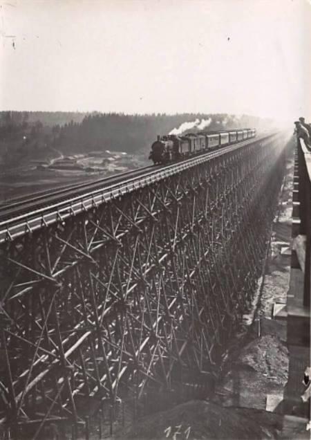 Vokiečiai stebi nuo naujojo tilto kaip mediniu geležinkelio tiltu per Dubysą Lyduvėnuose rieda traukinys, apie 1917-1918 m..jpg